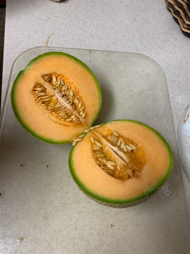 A ripe cantaloupe cut in half with seeds showing resting on a cutting board on a counter.